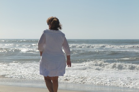 age 60: Back view of happy senior woman at the beach walking