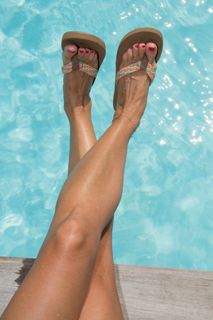 Woman shoes and legs on the pool relaxing