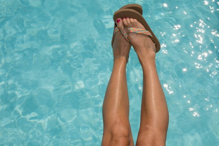 woman resting: Woman shoes and legs on the pool relaxing