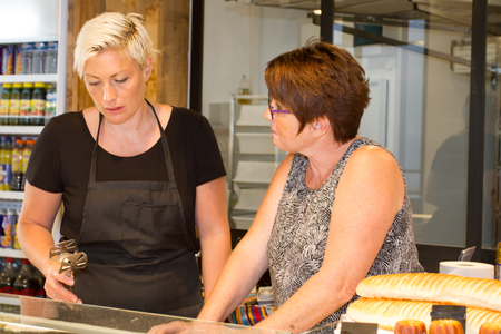 selling service: Two female baker or saleswoman in her bakery selling fresh bread, pastries and bakery products Stock Photo