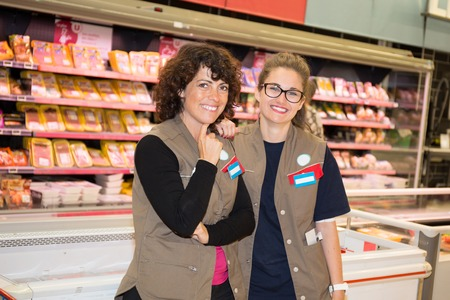 salespeople: Team of smiling happy salespeople in a supermarket Stock Photo