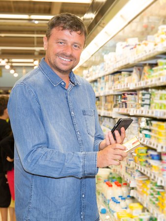 product information: Man shopping in supermarket reading product information