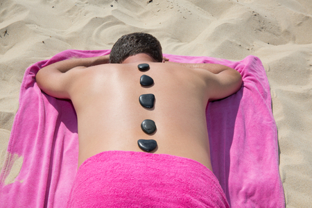 hot stones: Young man relaxing with hot stones on back before massage on beach