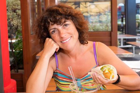 naive: Brunette woman eating hamburger in a restaurant