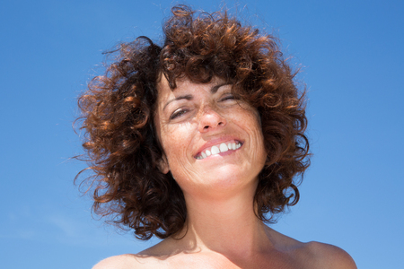 feeling up: Close up single woman wear standing and smile with happiness feeling under blue sky and sunlight in the afternoon