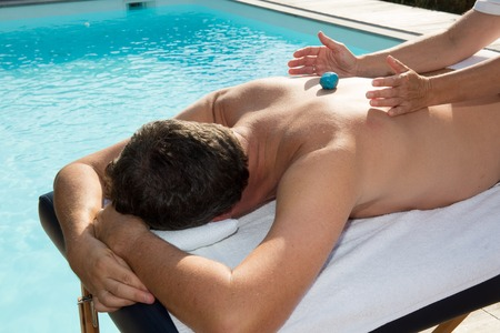 chakra energy: Man having crystals massage in a spa salon Stock Photo