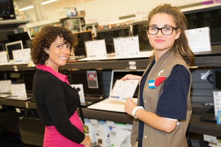 sales assistant: Woman department store choosing laptop with a sales assistant