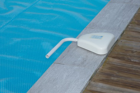 positioned: Swimming pool alarm positioned on the side of a deck