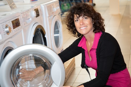 cargador frontal: Woman examining front loader of washing machine in shopping centre Foto de archivo