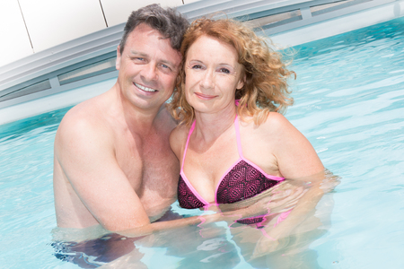 In love couple, middle aged relaxing by pool Stock Photo