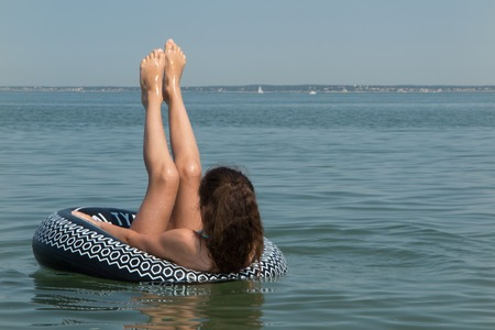 buoy: Girl in a black buoy in buoy with legs up