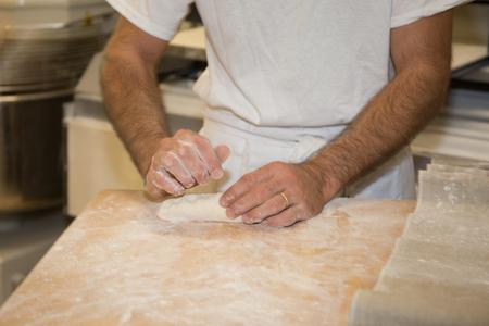 haciendo pan: panadero hacer pan, el hombre manos, amasando una pasta, cocinar escudo
