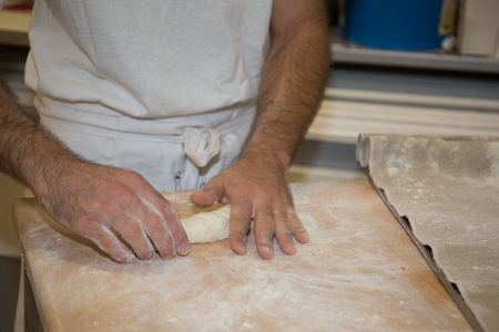 haciendo pan: baker making bread , man hands , kneading a dough , cooking coat Foto de archivo