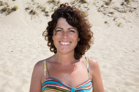 suntanned: Smiling suntanned woman on the background by sand. Summer day