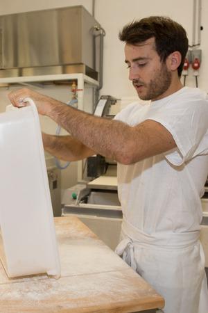 haciendo pan: Making bread by male baker at bakery Foto de archivo