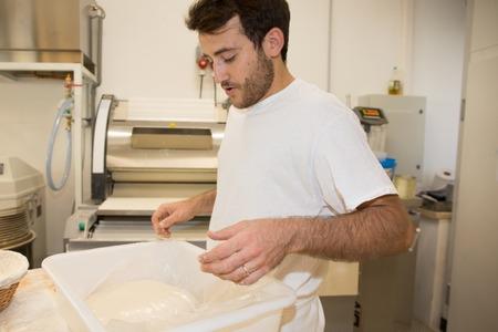 haciendo pan: Alegre hombre panadero haciendo pan en la panadería