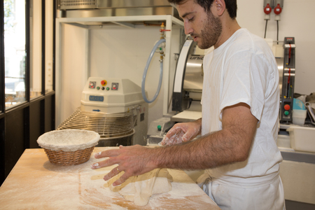 haciendo pan: Making bread by male baker at bakery Foto de archivo