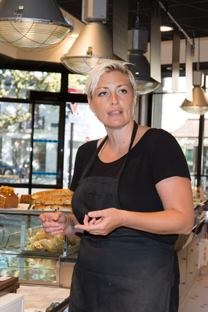 selling service: Confident Female baker or saleswoman in her bakery