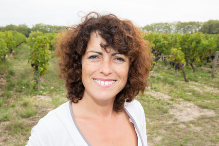 knelt: Middle aged woman harvester working in vineyard