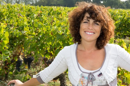 40 year old woman: Winegrower woman standing in vine rows Stock Photo