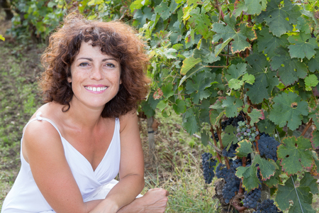40 year old woman: Winegrower happy and smiling woman in vine rows Stock Photo
