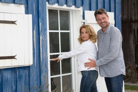 property owners: Cheerful new property owners in front of their house Stock Photo