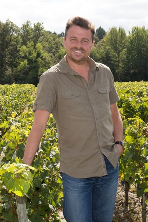 winemaker: Middle aged winemaker in vineyard with arms crossed