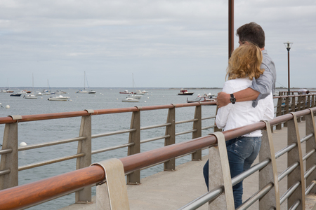 sea dock: Back view of a couple on a sea dock embracing