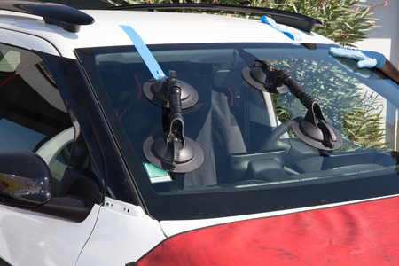 glazier: Repairman is repairing windshield of the car