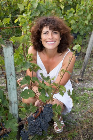 Winegrower Cheerful and smiling woman in vine rows