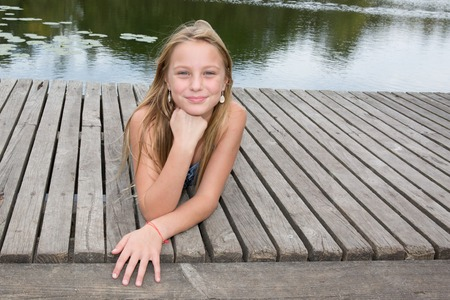 lost lake: Blond teen girl laying on pier on river