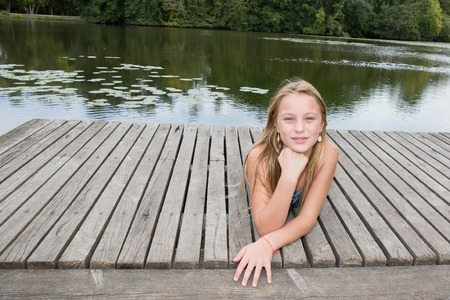 lost lake: Blond teen girl on pier on river in summer day Stock Photo