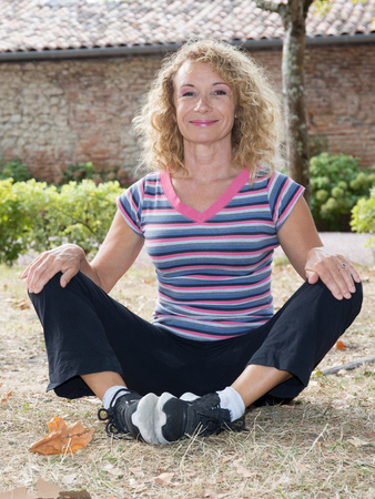 Smiling mature woman practicing yoga in the park