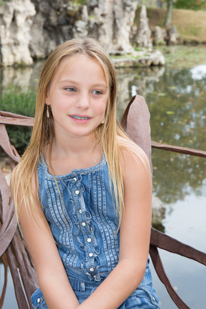 Young girl in a park setting smiles at the camera. Stock Photo