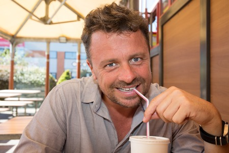 slurp: Smiling man drinking a frozen beverage at restaurant