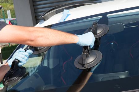 L'homme Mecanic évolue windscrenn sur une voiture Banque d'images - 64403758