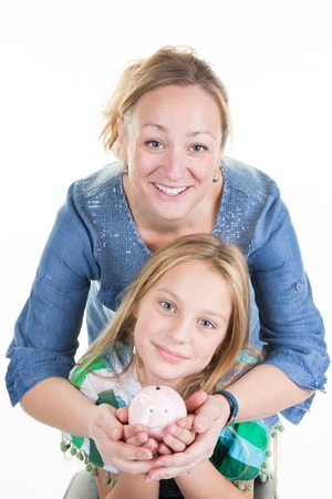 depositing: Happy mother and young girl holding piggy bank