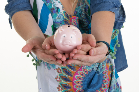 depositing: Mother and young girl holding piggy bank