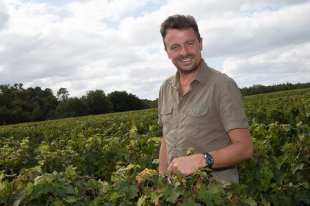 winemaker: Confident winemaker standing at family vineyard
