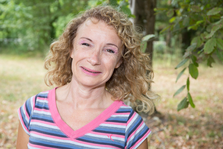 Blond smiling senior woman outdoor happy to be there