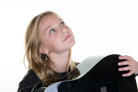 Young girl pr child holding a guitar, looking up