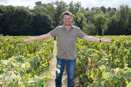 winemaker: Happy and smiling winemaker man in a his vineyard