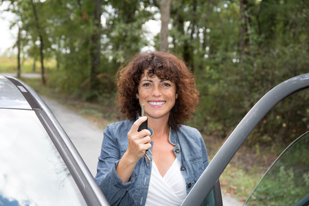 key handover: young smiling woman standing to the car taking key handover rent purchase