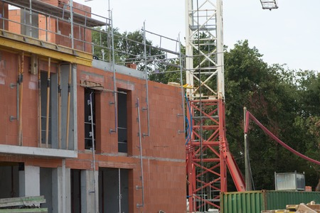 realestate: building and cranes under construction against blue sky