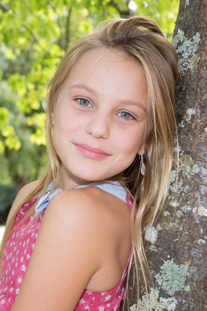 Pretty young girl looking out from behind a tree