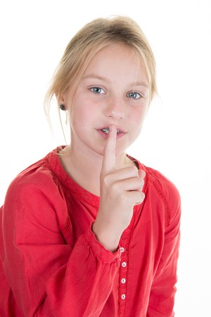 hushed: Blond girl in red putting finger up to lips saying silence isolated on white background