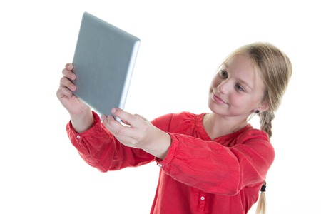 cheerfully: Girl cheerfully smiling, making selfie photo with tablet. Girl 8-10 year old