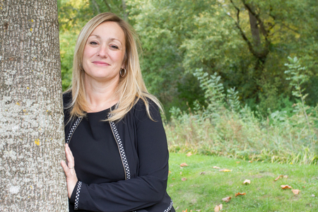 leaning against: Confident woman leaning against tree trunk Stock Photo