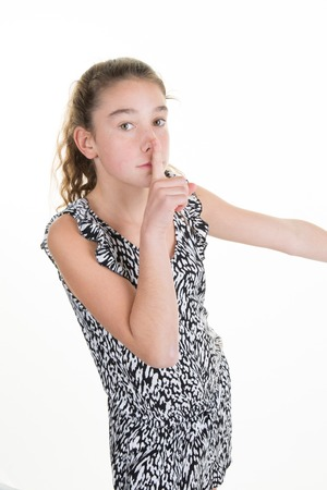 Young girl putting finger up to lips and ask silence isolated Stock Photo
