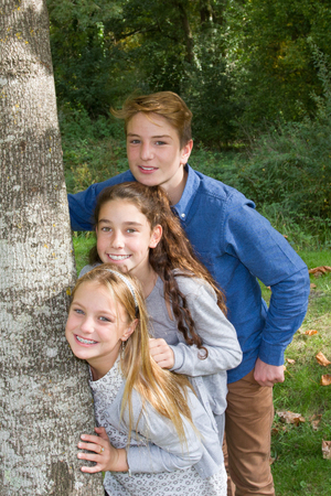 at close quarters: Brother and sisters outdoors smiling at park